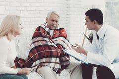 Giovane medico in cappotto che visita le vecchie coppie a casa immagine stock libera da diritti