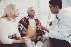 Giovane medico in cappotto che visita le vecchie coppie a casa fotografie stock libere da diritti