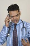 Giovane medico che comunica sul telefono mobile Immagini Stock