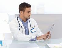 Giovane medico che per mezzo del computer della compressa Immagini Stock