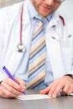 Giovane medico che scrive prescrizione medica Fotografia Stock