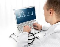Giovane medico con il computer portatile Fotografie Stock Libere da Diritti