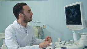 Giovane medico con la macchina di sistema diagnostico di ultrasuono Fotografie Stock