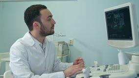 Giovane medico con la macchina di sistema diagnostico di ultrasuono archivi video