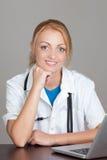 Giovane medico con lo stetoscopio facendo uso del computer portatile Immagine Stock Libera da Diritti
