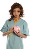 Giovane medico dell'afroamericano che tiene una banca piggy Immagine Stock Libera da Diritti