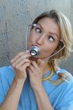 Giovane medico divertente che rende ad un fronte divertente con lei gli occhi attraversati Fotografie Stock