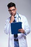Giovane medico esamina la lavagna per appunti preoccupata Fotografia Stock