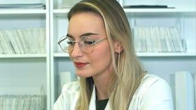 Giovane medico femminile attraente in vetri che si siedono allo scrittorio in ufficio Fotografie Stock