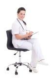Giovane medico femminile che si siede sopra il fondo bianco Fotografie Stock Libere da Diritti