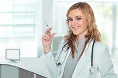 Giovane medico femminile che sorride con una siringa in sua mano Immagini Stock