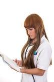 Giovane medico femminile con il libro di lettura dello stetoscopio Fotografie Stock
