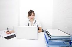 Giovane medico femminile con le note di scrittura del computer portatile sullo scrittorio in clinica Fotografie Stock