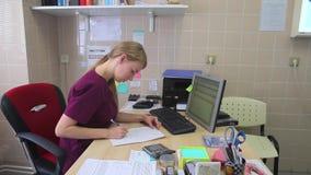 Giovane medico femminile scrive su carta per il desktop video d archivio