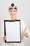 Giovane medico femminile serio con un dispositivo di piegatura Immagini Stock