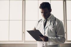 Giovane medico indiano nelle note di scrittura dell'uniforme di bianco immagini stock libere da diritti