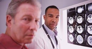 Giovane medico intelligente che esamina macchina fotografica con il metà di paziente invecchiato fotografie stock