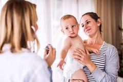 Giovane medico, madre e un neonato in un ufficio fotografie stock libere da diritti