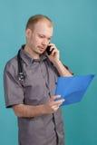 Giovane medico maschio che tiene una cartella con le carte e che parla sul telefono su fondo blu Fotografia Stock