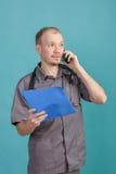 Giovane medico maschio che tiene una cartella con le carte e che parla sul telefono su fondo blu Immagini Stock