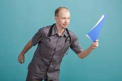 Giovane medico maschio che tiene una cartella con le carte su fondo blu Fotografie Stock Libere da Diritti