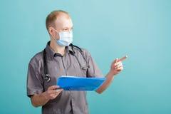 Giovane medico maschio che tiene una cartella con le carte su fondo blu Fotografia Stock