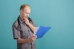 Giovane medico maschio che tiene una cartella con le carte su fondo blu Fotografia Stock Libera da Diritti