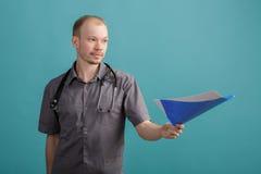 Giovane medico maschio che tiene una cartella con le carte su fondo blu Immagine Stock