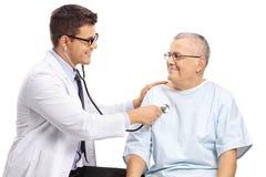Giovane medico maschio facendo uso di uno stetoscopio su un paziente anziano immagini stock