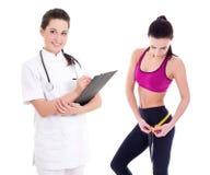 Giovane medico o dietista femminile con la donna esile in abiti sportivi i fotografie stock