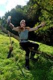 Giovane medievale vestito un uomo, corno bevente delle tenute a disposizione, entrambe le armi distese Fotografia Stock Libera da Diritti