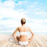 Giovane, meditare sportivo, adatto e bello della ragazza isolato su whi Immagine Stock