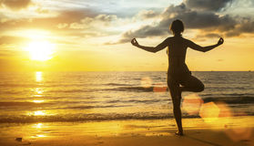 Giovane meditazione della siluetta della donna di yoga sulla spiaggia al tramonto nave Immagini Stock