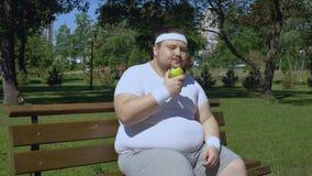 Giovane mela mangiatrice di uomini grassa dopo avere pareggiato all'aperto, pranzo adeguato con le vitamine archivi video