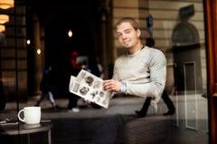 Giovane menu al caffè con la tazza di caffè sulla tavola, riflessione della lettura della persona di sesso maschile in finestra Fotografia Stock