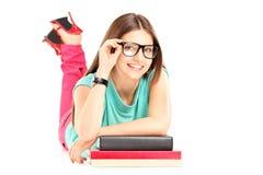 Giovane menzogne femminile sui libri ed esaminare macchina fotografica Fotografie Stock