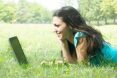 Giovane menzogne femminile sull'erba per mezzo di un computer portatile Immagine Stock Libera da Diritti