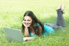 Giovane menzogne femminile sull'erba per mezzo di un computer portatile Immagini Stock Libere da Diritti