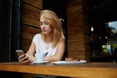 Giovane messaggio di testo femminile caucasico della lettura sul suo telefono cellulare mentre sedendosi nell'interno moderno del Fotografia Stock Libera da Diritti
