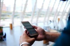 Giovane messaggio di testo maschio della lettura sul telefono delle cellule mentre stando nel corridoio aspettante dell'aeroporto Fotografia Stock