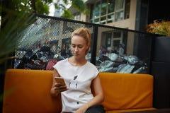 Giovane messaggio di testo splendido della lettura della donna sul suo telefono cellulare mentre sedendosi da solo nella barra de Fotografia Stock
