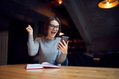 Giovane messaggio femminile emozionante e sorpreso della lettura sul cellulare Fotografia Stock
