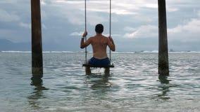 Giovane misura ed uomo attraente che godono delle vacanze estive che si siedono sull'oscillazione del mare alla stazione balneare archivi video