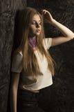 Giovane modello alla moda con capelli biondi fertili che posano nel roo scuro Fotografia Stock