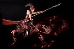 Giovane modello asiatico in vestiti nazionali dei nomadi nella sella che possing nello studio fotografia stock