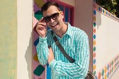 Giovane modello bello di risata felice sicuro alla moda dell'uomo in t-breve blu con gli occhiali da sole Priorità bassa del reti Fotografia Stock