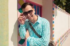 Giovane modello bello di risata felice sicuro alla moda dell'uomo in t-breve blu con gli occhiali da sole Priorità bassa del reti Fotografie Stock Libere da Diritti