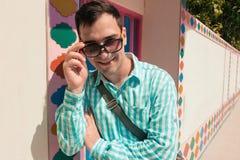 Giovane modello bello di risata felice sicuro alla moda dell'uomo in t-breve blu con gli occhiali da sole Priorità bassa del reti Immagini Stock