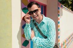 Giovane modello bello di risata felice sicuro alla moda dell'uomo in t-breve blu con gli occhiali da sole Priorità bassa del reti Immagini Stock Libere da Diritti