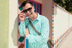 Giovane modello bello di risata felice sicuro alla moda dell'uomo in t-breve blu con gli occhiali da sole Priorità bassa del reti Fotografia Stock Libera da Diritti